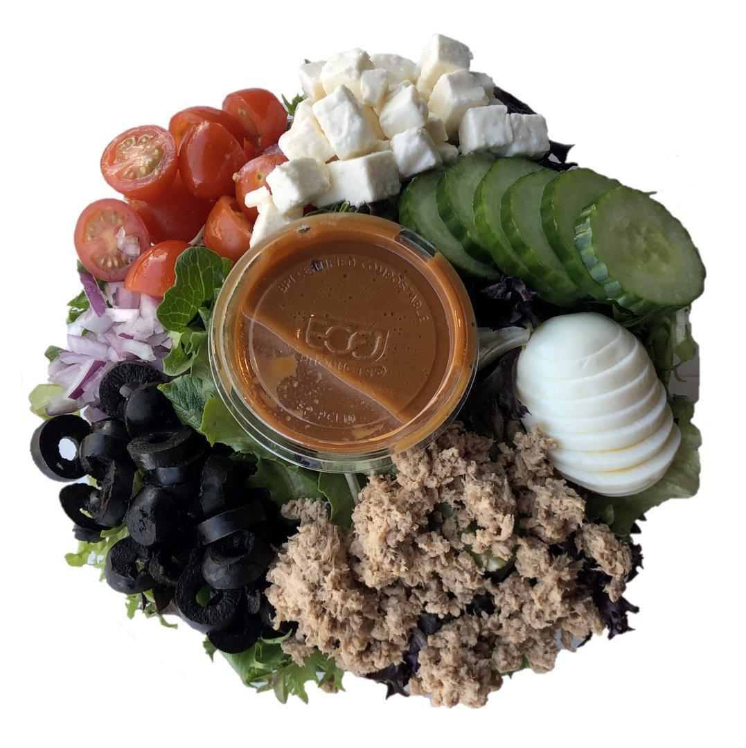 Salade express d'avril : Laitue mixte, oeuf dur, thon, feta, olive noire, concombre, tomate & oignon rouge. Servi avec notre vinaigrette Chili doux